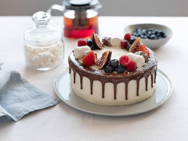Deliziosa torta con marshmallow ai frutti di bosco e teiera sulla tovaglia di lino compleanno festa della mamma