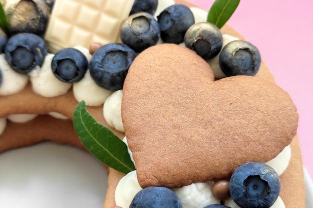 Deliziosa torta a forma di san valentino decorata con mirtilli e cioccolato bianco