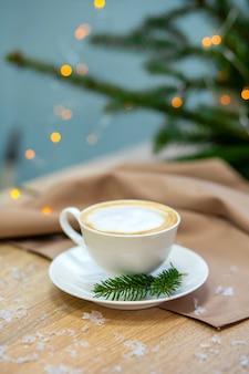 Deliziosa tazza da caffè cappuccino. lucciole e rami di abete rosso.