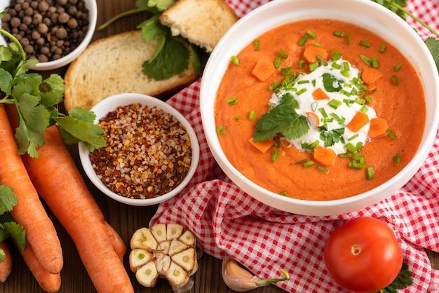 Deliziosa zuppa di carote con diversi condimenti e additivi di carote fresche.