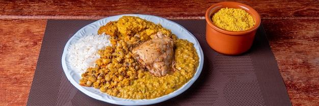 Delicious caruru. piatto tradizionale afro-brasiliano a base di gombo e gamberi secchi, accompagnato da vatapa, fagioli, riso, pollo e farofa. su un tavolo di legno.