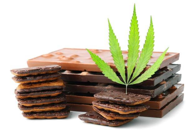 Delizioso biscotto con gocce di cioccolato e cannabis cbd, decorazione di foglie di canapa verde. trattamento di marijuana medica per il consumo umano.