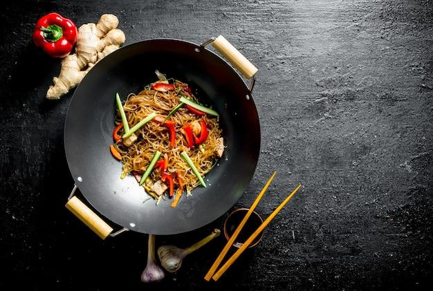 Deliziose tagliatelle di cellophane in una padella wok con le bacchette sul tavolo rustico nero