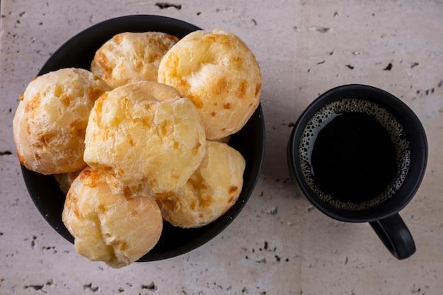 Deliziosi panini al formaggio e una tazza di caffè su marmo bianco - vista dall'alto.