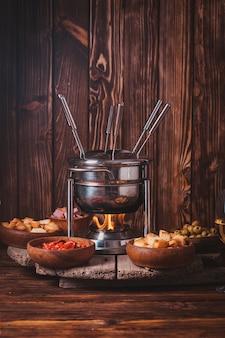 Deliziosa fonduta di formaggio su una forchetta su un supporto di legno