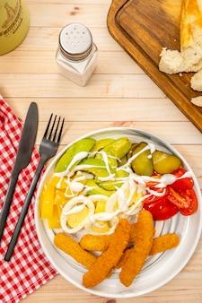 Deliziosi bastoncini di pollo con insalata di avocado, pomodorini, formaggio manchego, uova e cetrioli in agrodolce con salsa alioli. vista aerea, orientamento verticale. copia spazio.