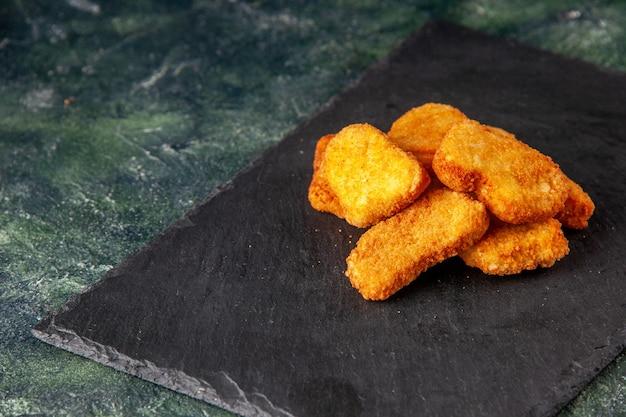Deliziose crocchette di pollo su vassoio nero sul lato sinistro su superficie di colore scuro con spazio libero