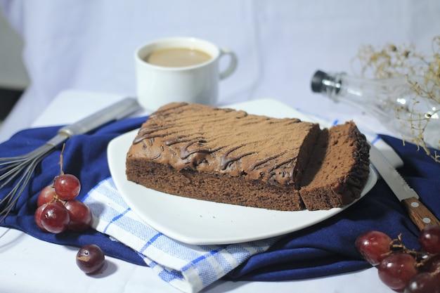 Deliziosi brownie al cioccolato su un piatto bianco con un bicchiere di uva da caffè e un coltello intorno