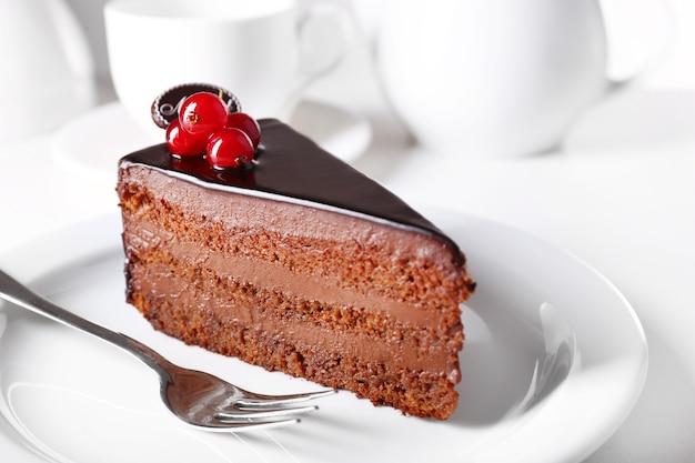 Deliziosa torta al cioccolato sulla piastra sul tavolo sulla luce