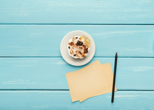 Deliziosa torta al cioccolato su piatto bianco, penna e piccoli fogli per messaggi romantici su tavolo in legno turchese, vista dall'alto, spazio copia
