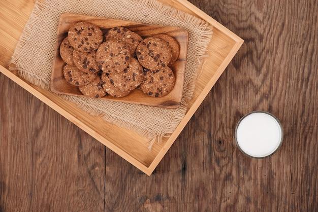Deliziosi biscotti con scaglie di cioccolato su un vassoio su un vecchio tavolo di legno scuro
