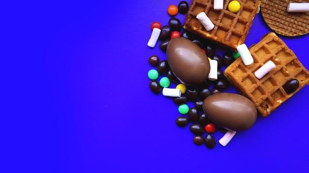 Deliziose uova di pasqua al cioccolato, waffle, dolci su sfondo blu scuro