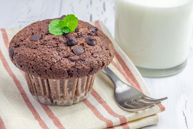 Muffin delizioso del cioccolato con il primo piano delle patatine fritte e del bicchiere di latte di choco