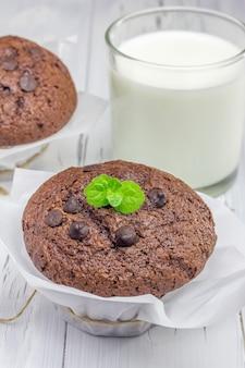 Muffin al cioccolato deliziosi con scaglie di cioccolato e bicchiere di latte