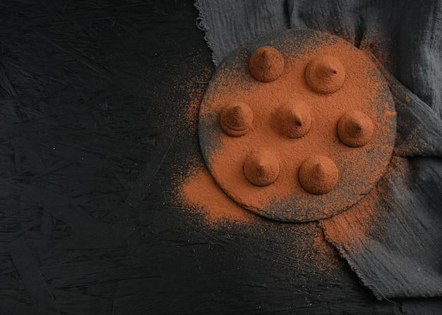 Deliziosi tartufi al cioccolato su sfondo nero.
