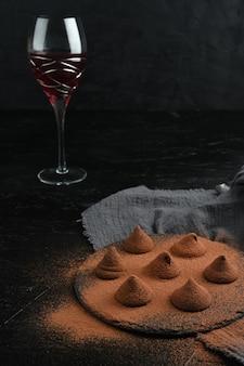 Deliziosi tartufi al cioccolato e vino rosso su sfondo nero.