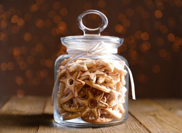 Deliziosi biscotti di natale in barattolo sul tavolo su sfondo marrone