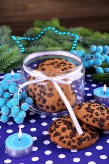 Deliziosi biscotti di natale in barattolo sul tavolo su fondo di legno