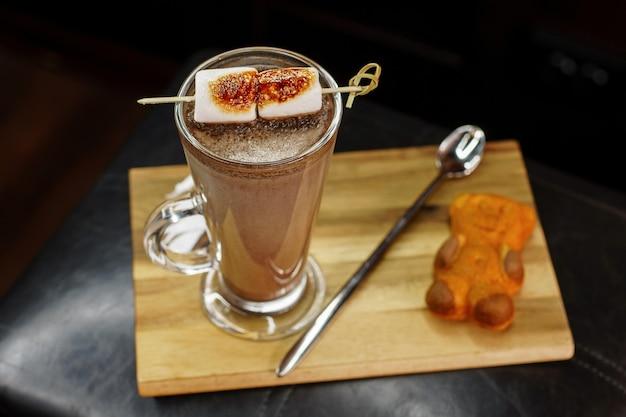 Delizioso cocktail di caffè con marshmallow con biscotti di orsacchiotto su una tavola di legno