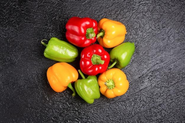 Deliziosi peperoni colorati sulla tavola nera