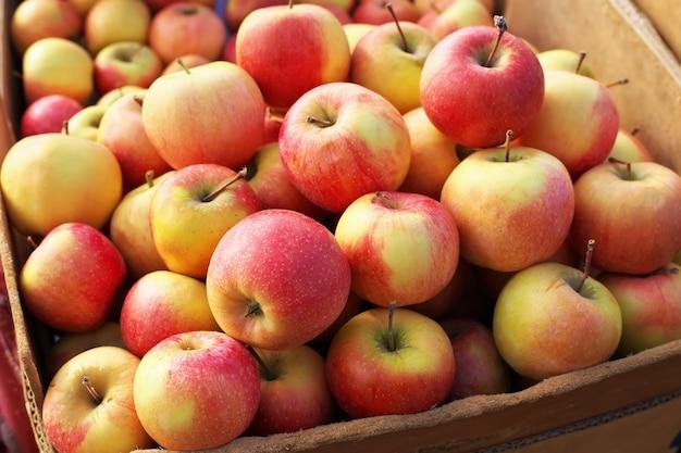 Deliziose mele agrodolci colorate nella scatola sul mercato