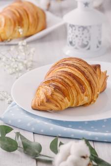 Deliziosa colazione continentale con croissant francesi freschi a fiocchi, primi piani sui croissant. con fiori di cotone bianco. stile rustico provenzale.