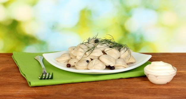 Deliziosi gnocchi cotti nel piatto su sfondo verde brillante