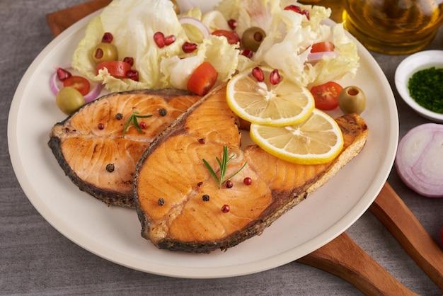 Deliziosi filetti di salmone cotto. filetto di pesce salmone alla griglia e insalata di pomodori verdure fresche di lattuga verde. concetto nutrizionale equilibrato per un'alimentazione pulita dieta mediterranea flessibile.