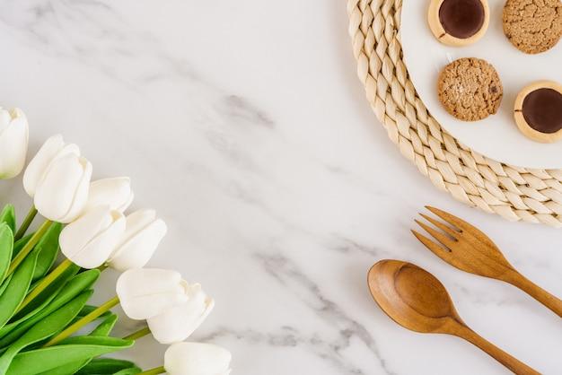 I biscotti deliziosi su un piatto bianco con il cucchiaio e la forchetta di legno sono disposti accanto ai biscotti e ai tulipani bianchi sul fondo di marmo della tavola con uno spazio della copia. disteso. design minimalista. orizzontale.