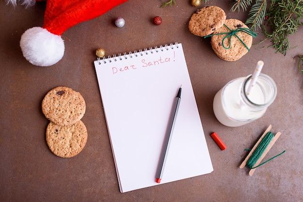 Deliziosi biscotti con cioccolato su un piatto bianco, latte, cappello da babbo natale, mock up per il testo. lettera e biscotti per babbo natale.