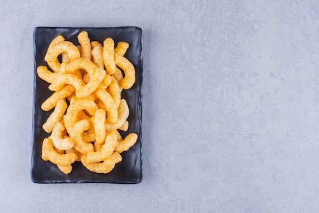 Deliziosi bastoncini di mais su un piatto sulla superficie blu
