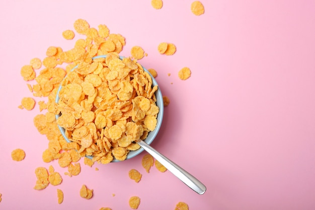 Deliziosi fiocchi di mais in un piatto su sfondo colorato