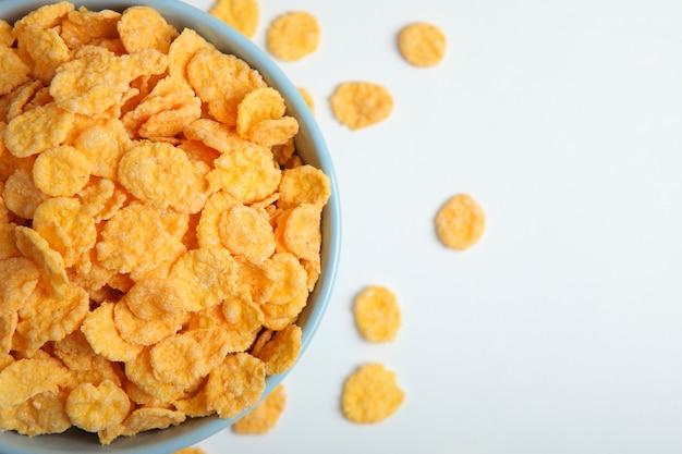 Deliziosi cornflakes in un piatto su sfondo chiaro