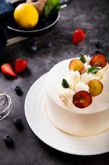 Torta cremosa deliziosa con le bacche sulla tabella nera di lusso