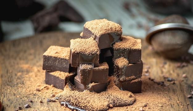 Deliziosi cubetti di cioccolato fondente amaro cosparsi di cacao in polvere su un tavolo di legno.