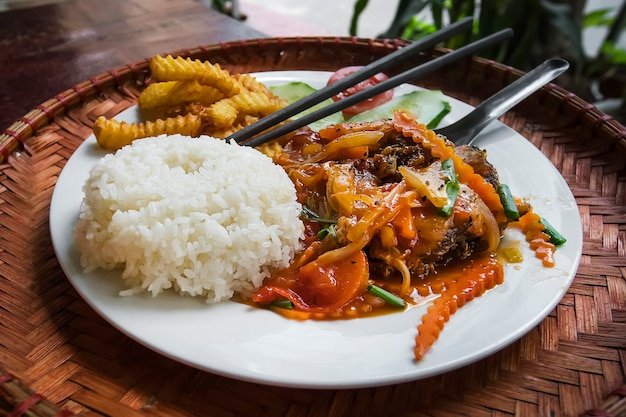 Cucina deliziosa. un piatto di riso bollito con frutti di mare fritti con verdure su un tavolo in un ristorante di strada in vietnam. cibo vietnamita piccante. curry con riso. bacchette nel riso.