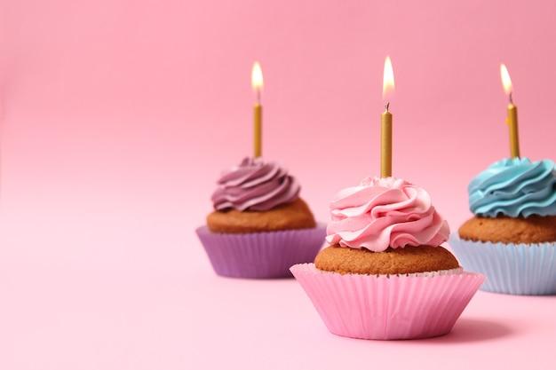 Delizioso cupcake con candela su sfondo colorato