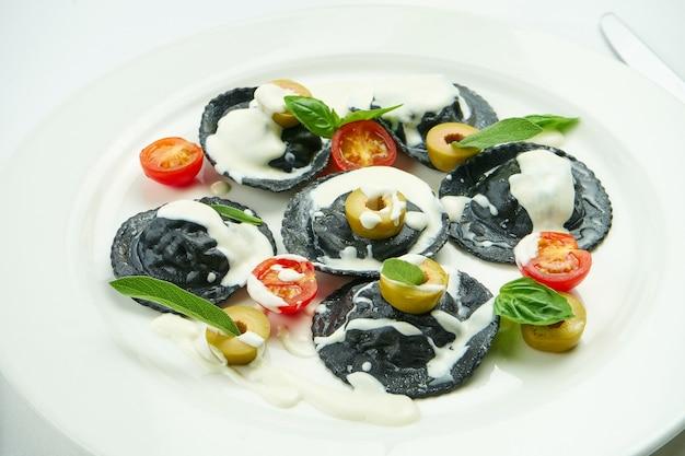 Deliziosi ravioli al nero di seppia ripieni di gamberi e capesante, serviti con salsa bianca, pomodorini e olive in un piatto bianco su tovaglia bianca