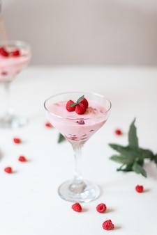 Delizioso dessert, cheesecake con lamponi freschi e mousse di crema di burro in vetro su un tavolo bianco. copia spazio