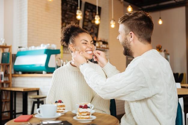 Deliziosi dessert. coppia carina che indossa gli stessi maglioni mangiando deliziosi dessert e bevendo latte