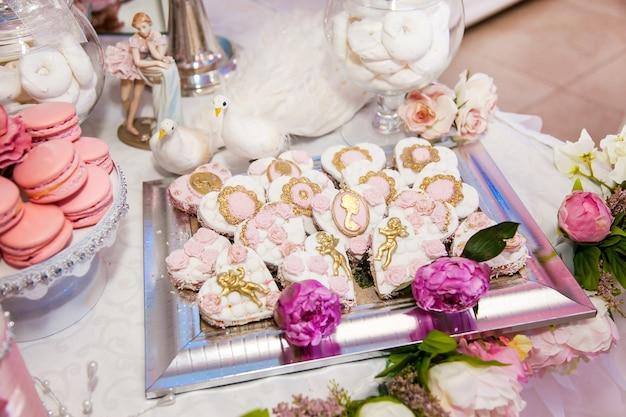 Deliziosi dessert al wedding candy bar nell'area buffet: biscotti ricoperti di glassa, decorati con angeli, cammeo, boccioli di rosa di zucchero e colorante oro.