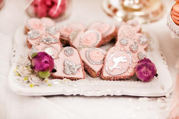 Deliziosi dessert al wedding candy bar nell'area buffet: biscotti ricoperti di glassa, decorati con angeli, cammeo, roselline di zucchero e colorante argento