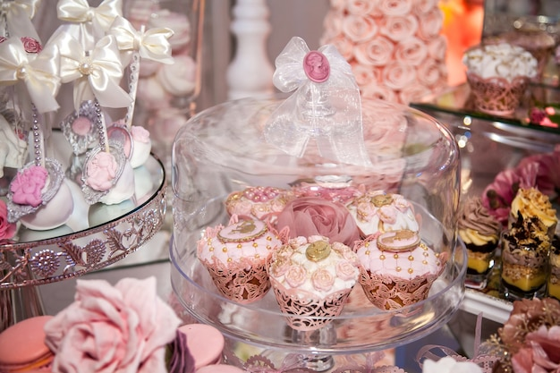 Deliziosi dessert al wedding candy bar nell'area buffet: muffin decorati con angeli, cammeo, roselline di zucchero e colorante oro.