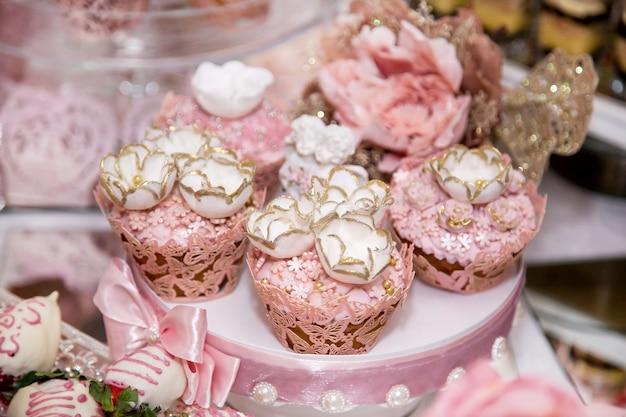 Deliziosi dessert al wedding candy bar nell'area buffet: muffin decorati con angeli, roselline di zucchero e colorante oro