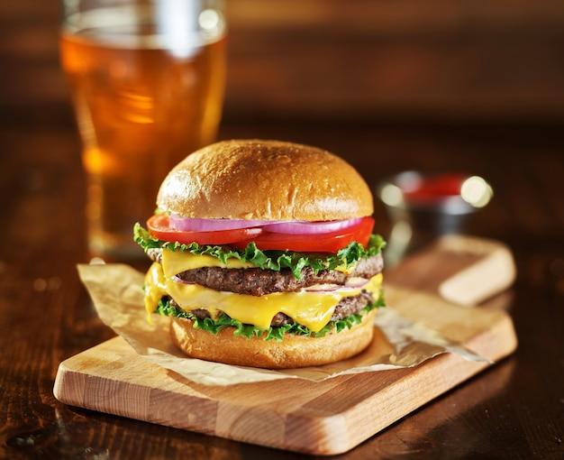 Delizioso doppio cheeseburger su una tavola di legno