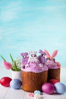 Deliziosi dolci pasquali decorati con glassa di coniglio, canditi e meringhe e uova di gallina su turchese con spazio di copia