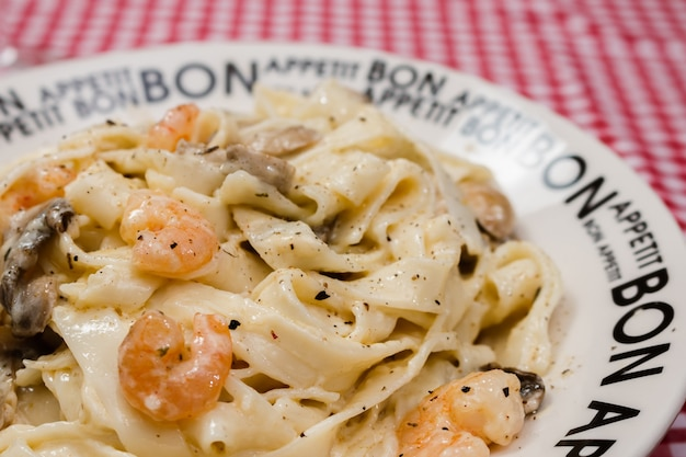 Deliziose fettuccine con salsa alla panna di funghi e gamberi su un piatto con la scritta bon appetite con tovaglia a quadretti rossa. cucina italiana. Foto Premium