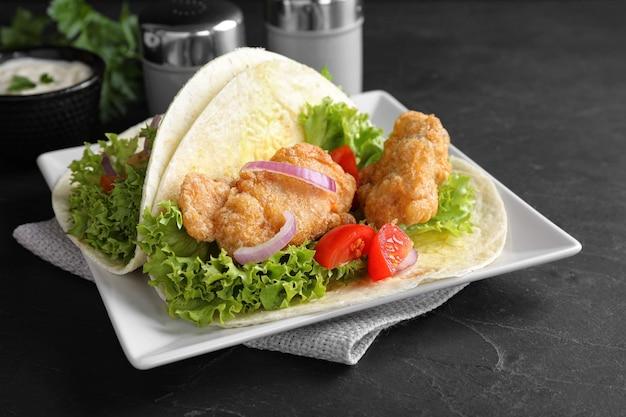 Deliziosi tacos di pesce serviti su un tavolo scuro