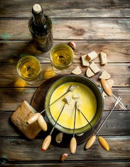 Deliziosa fonduta con fette di pane e vino bianco. su uno sfondo di legno.