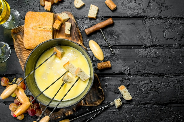 Deliziosa fonduta di formaggio con vino bianco su tavola rustica nera.